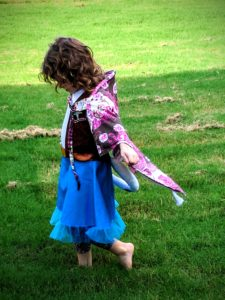 Preschool-aged girl wearing nursing cover as a cape