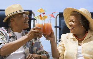 Old couple sitting on beach chairs toasting tall tropical cocktails