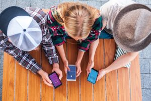 Women looking at their phone checking social media | Home a la Mama