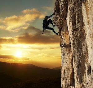 Overcoming Obstacles. Woman climbing a mountain with sunset in the back.