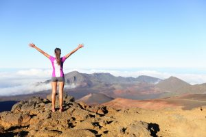Overcoming obstacles by leaving her comfort zone. A Hiking woman on top happy and celebrating success. Female hiker on top of the world cheering in winning gesture having reached summit of mountain, East Maui Volcano, Haleakala national park Hawaii.