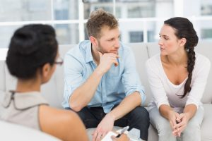 Unhappy couple at therapy session in therapists office during difficult seasons in marriage