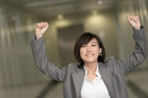 Excited and confident woman smiling with fists in the air.