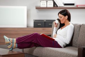 Young Woman Lounging in Living Room on Couch reading book and drinking coffee