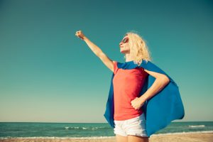 Woman standing on Beach with a cape.