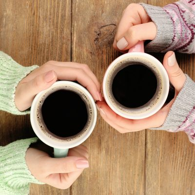 Two women's hands holding cup of coffee as they talk about being a good friend to a newly single mom