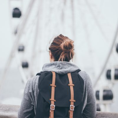 Woman with backpack staring off at a ferris wheel. Having sold what she owns. She longs to learn lessons from the Bible about the rich young ruler.