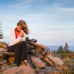 beautiful woman praying on the top of a mountain using the Model Prayer as a step by step guide